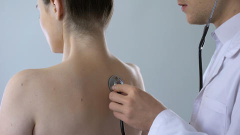 Physician listening to lungs with stethoscope, woman breathing heavily back view Live Action