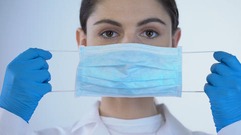 Young female doctor wearing surgical mask, safety while examining, closeup Archivo