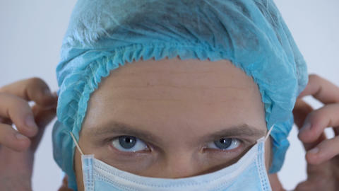 Male physician wearing surgical mask, preparing for patient examination, closeup Live Action