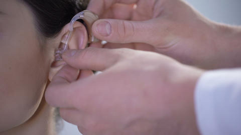 Closeup of ear with hearing aid, young deaf woman adjusting to environment Footage