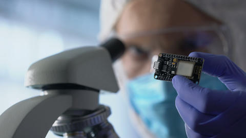 Technician examining chip, using microscope to run diagnosis and upgrade device Footage