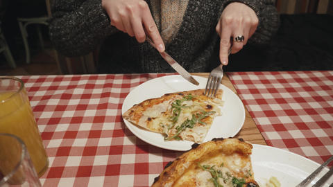 Hungry woman eating pizza using fork and knife in a restaurant Footage