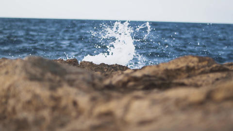 Foamy waves breaking on the rocks. Waves hit rocky shore close up Live Action
