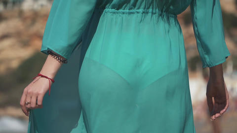 Woman with black hair standing back to camera in transparent turquoise dress on Live Action