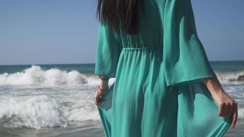 Woman with a perfect body wearing turquoise dress walks into the sea. Dress Footage