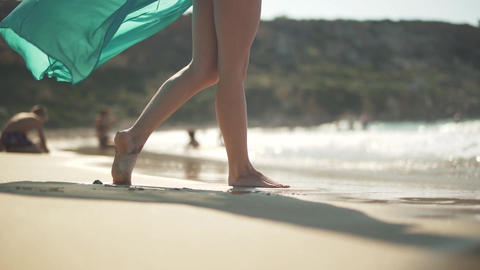 Female bare feet walking on the wet sand on the beach. Female legs posing in the Live Action