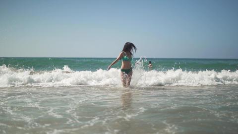 Pretty woman with dark hair and perfect body wearing sunglasses and bikini runs Footage