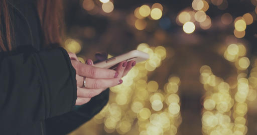Close-up shot of woman hands with smartphone in the city at night. Technology Footage