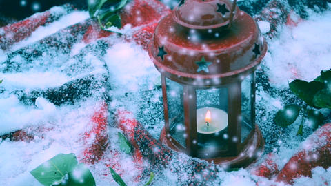 Red candle lantern with candle in snow during snowfall Archivo