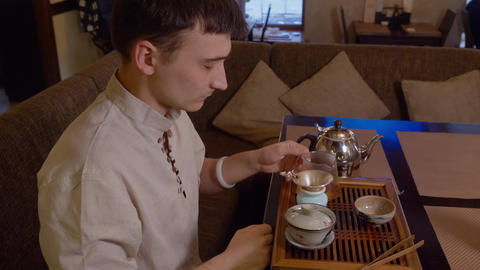 Master pours hot water in bowl and rinses for tea brewing to japanese tradition Live Action