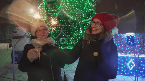 Mother and daughter dancing with sparklers under the snowfall near the Christmas Footage