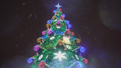 Snow covered christmas tree with multi colored lights at night in 4k Footage