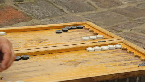 Aged retired men playing backgammon in the yard outside, board games enjoyment Live Action