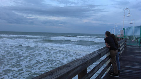 Young couple relaxing on the pier - DAYTONA BEACH, FLORIDA APRIL 14, 2016 Live Action