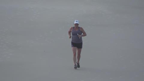 Young woman jogging at the beach - DAYTONA BEACH, FLORIDA APRIL 14, 2016 Live Action