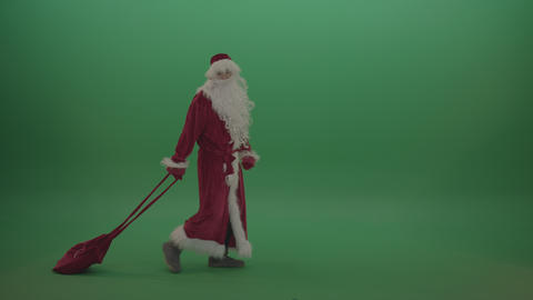 Santa graciously walks across with gift bag over chromakey background Live Action