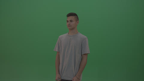 Boy in grey wear expresses fright over green screen background Live Action