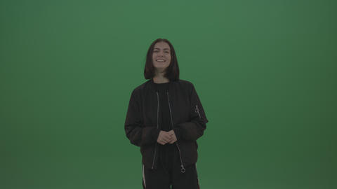 Girl in black wear smiles as she poses over chromakey background Footage