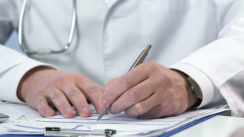 Close-up of doctors hands filling registration form, medicine and healthcare Live Action