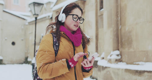 Woman listen to music on mobile phone in the city at winter time. Attractive 영상물