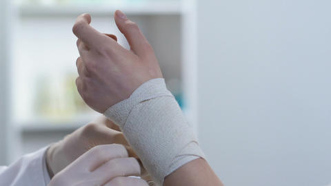 Traumatologist bandaging patient wrist, stretching muscles, first aid course Footage