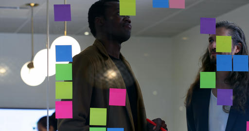Business colleagues discussing over sticky notes in office 4k Live Action