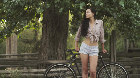 Young woman standing with a bicycle outdoor 영상물