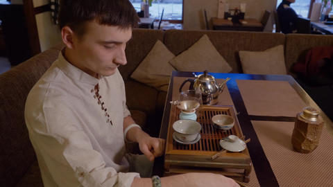 Tea master sniff tea leaves in golden bronze chahai and pour it to ceramic Live Action