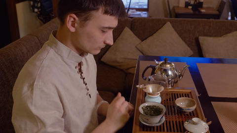 Tea master pour hot water from kettle to gaiwan with leaves of green tea Live Action