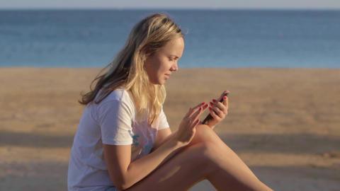 girl with mobile phone at the beach at summer travel at the sea Live Action