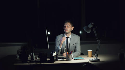 Weary guy office worker is working on computer late at night meeting deadline Live Action