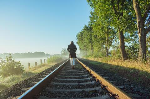 Single woman is running on railway tracks towards the horizon フォト