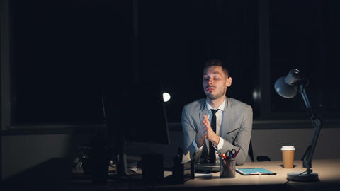 Tired young man in suit is working on computer late at night sitting in office Live Action