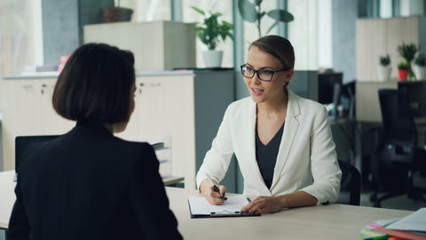 Good-looking young lady from human resources department is interviewing a female Live Action