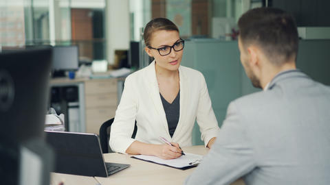 Friendly businesswoman in glasses and suit is interviewing a male candidate for Footage