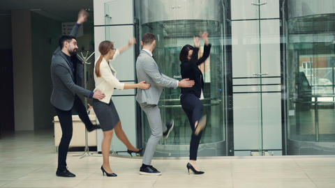 Laughing men and women businesspeople are having fun at office party dancing in Footage