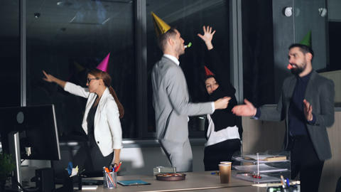 Happy young people office workers are dancing at company party wearing party Live Action