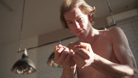 Young naked man squeezing orange in his strong hands. Orange juice flows in Live Action
