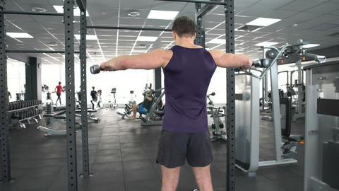 Sportsman lifting dumbbells sport club, lateral raise exercise, active leisure Footage