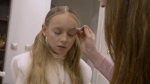 Makeup artist doing make up face young girl teenager in beauty studio Footage
