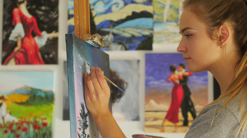 Smiling female artist paints picture on canvas with oil paints Footage