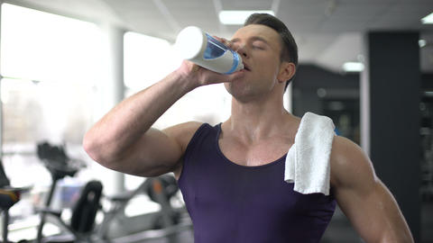 Sweaty sportsman drinking water after workout, healthy nutrition, aqua balance Live Action