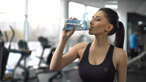 Sport lady drinking water after gym training, aqua balance, healthy nutrition Live Action