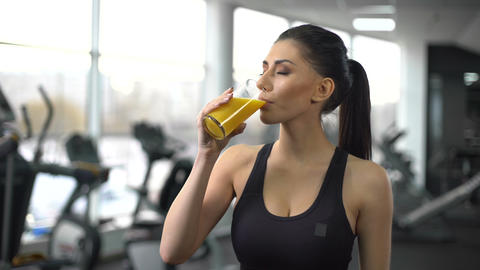 Fit woman drinking refreshing juice from glass after gym workout, health care Footage