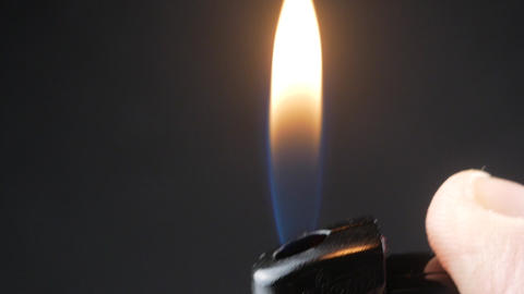 Hand holding burning gas lighters on dark background, Portable device used to Live Action