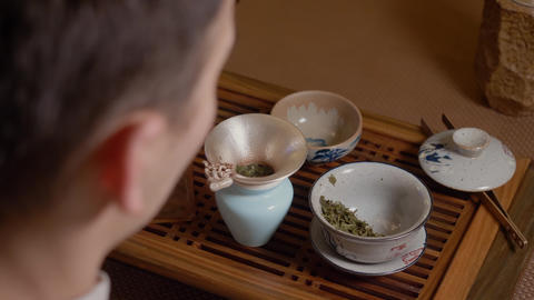 Tea master pours hot water from kettle to gaiwan. Steam from hot cup. Green tea Footage