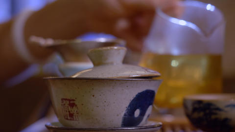 Master pouring tea infusion from fairness bowl in cup. Chinese tea ceremony Live Action