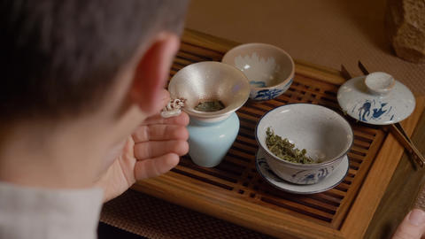 Tea master pours infusion from fairness cup into bowl and drinks chinese tea Live Action