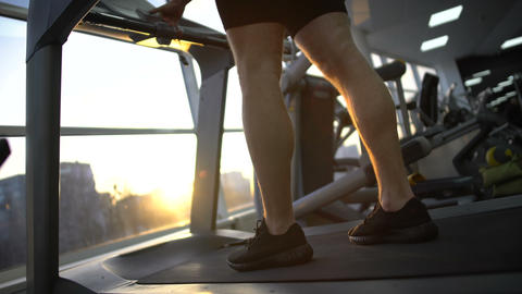Athlete man running on treadmill in gym, warming up before workout, health ビデオ