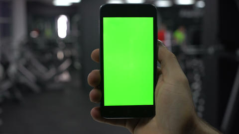 Male hand with smartphone in gym, fitness application results, green screen Footage